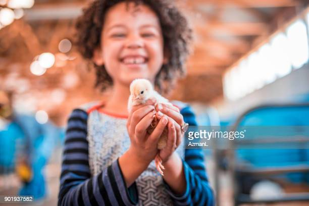 Holding chicken in her hands