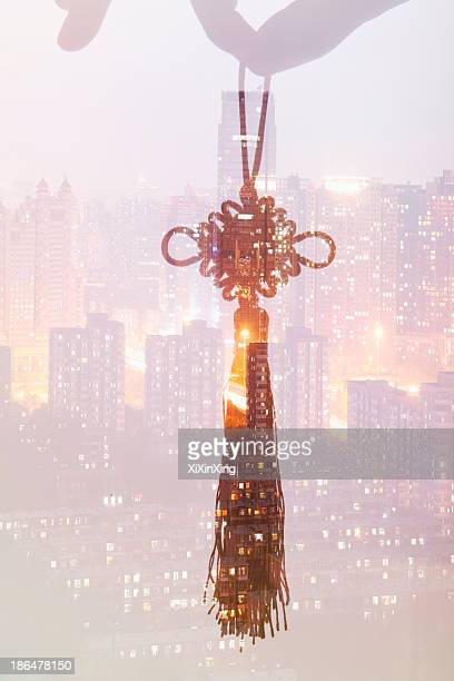 holding chinese knot, night city view - chinese knotting stock pictures, royalty-free photos & images
