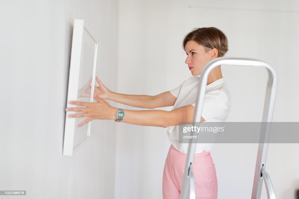 Holding framed picture against the white wall : Stock Photo