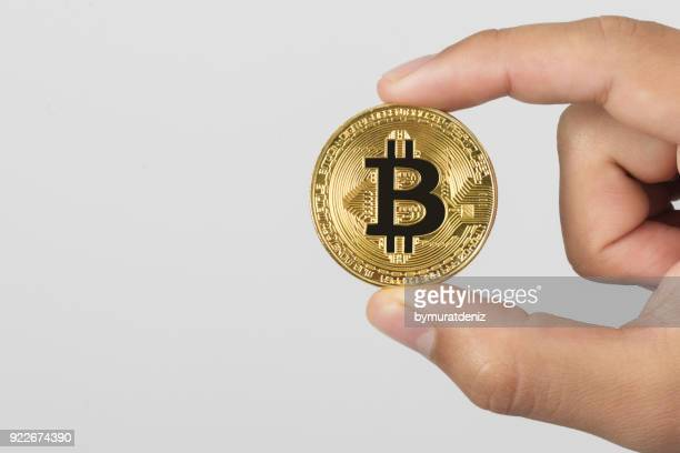 Holding golden coin of bitcoin