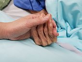 Holding grandmother's hand in the nursing care. Showing all love, empathy, helping and encouragement : healthcare in end of life and palliative concept