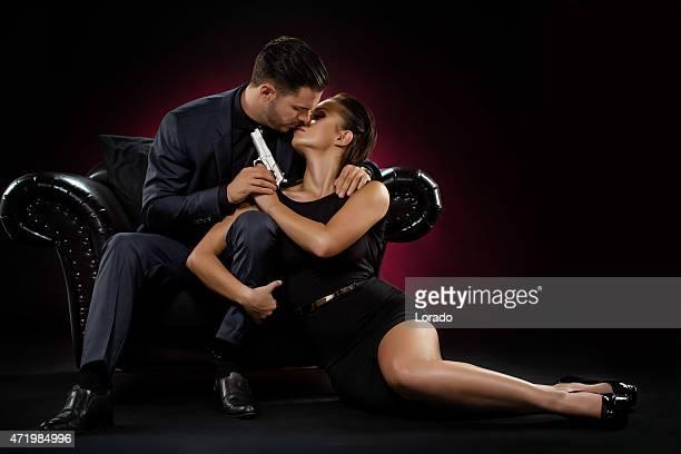 holding gun couple kisses