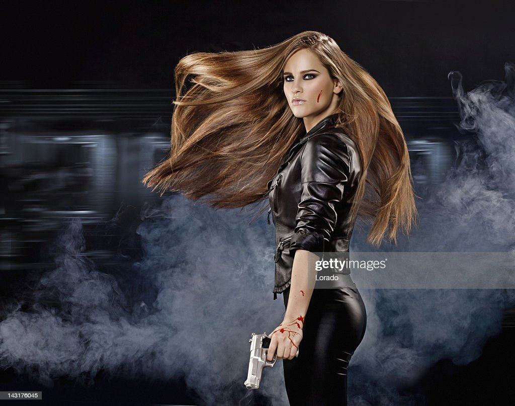 Holding gun sexy woman with long flying hair : Stock Photo