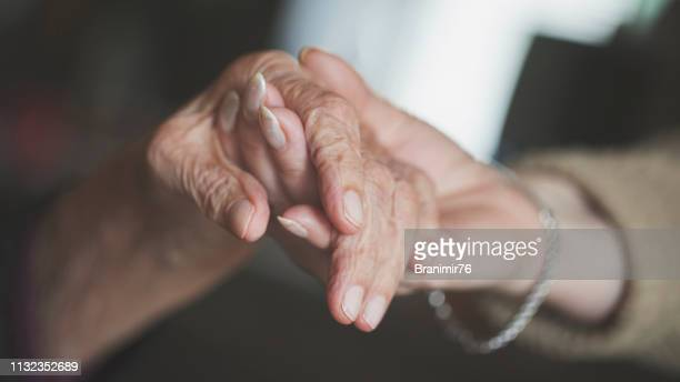 holding hand of very old woman-home caregiver - alzheimer's disease stock pictures, royalty-free photos & images