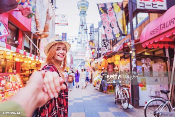holding hands and exploring famous streets of shinsekai, osaka, japan - osaka prefecture stock pictures, royalty-free photos & images