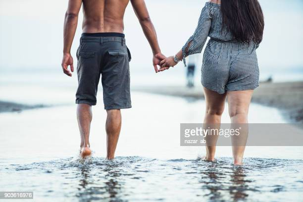 Holding hands and walking in water.