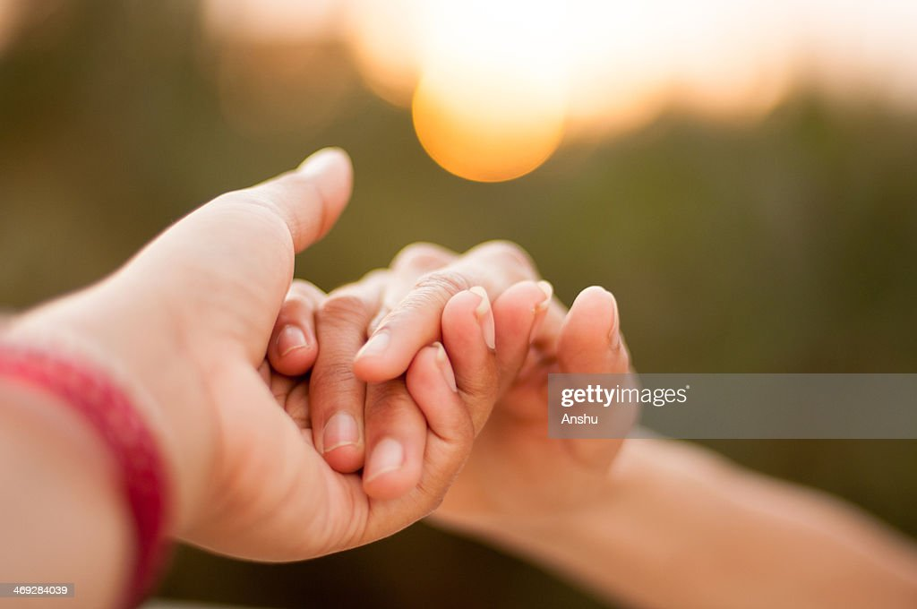 Holding hands during sunset : Stock Photo