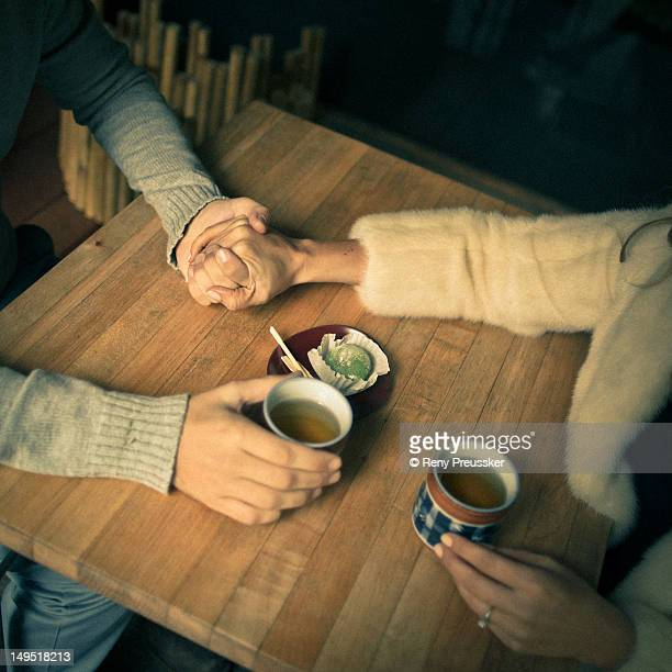 Holding hands over tea