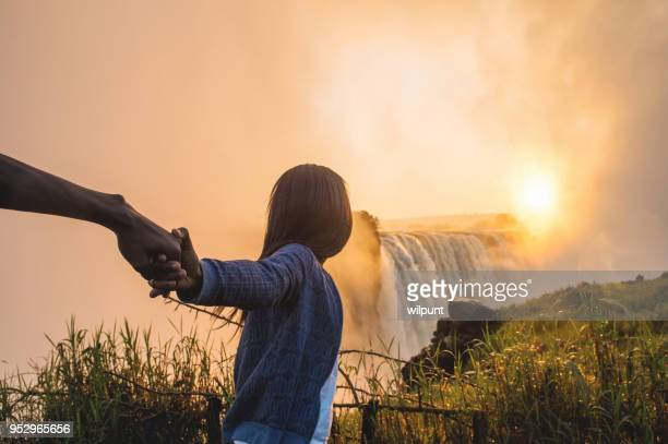 holding hands pulling and looking towards a sunrise over victoria falls - victoria falls stock pictures, royalty-free photos & images