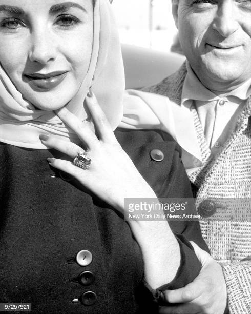 Holding her arm and gazing at her solicitously Mike Todd squires his love Elizabeth Taylor to plane at International Airport Liz and Mike flew to...