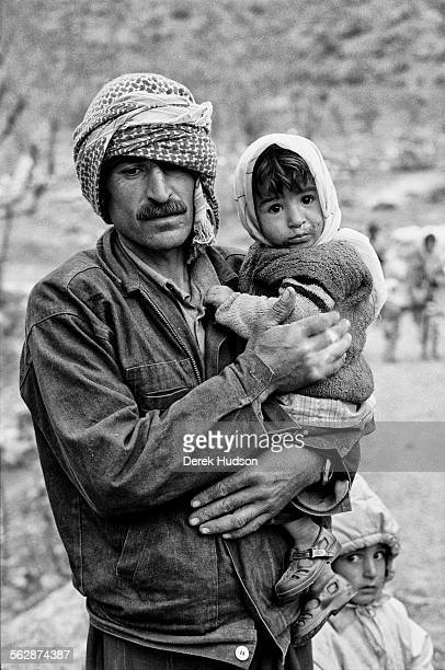 Holding his baby girl child a Kurdish man and his son on the road towards the camp site at Isikveren Turkey where thousands of Kurds landed up after...