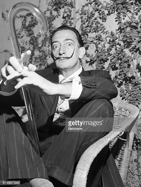 Holding his famous glass walking stick surrealist painter Salvador Dali meets newsmen at his Rome hotel He is in the Eternal City in connection with...