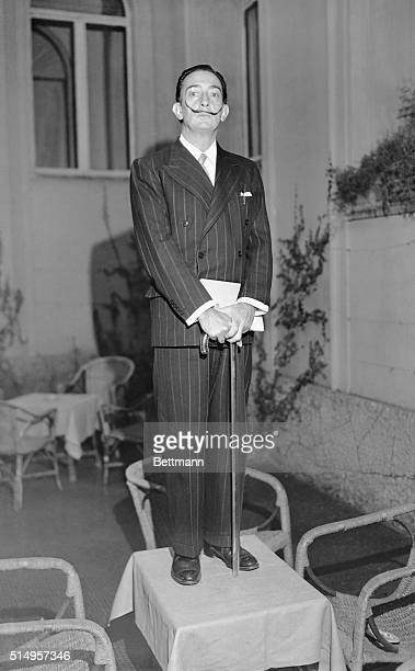 Holding his famous glass walking stick surrealist painter Salvador Dali meets newsmen at his Rome hotel He is in the Eternal City in connections with...