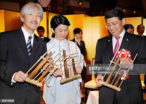 Holding Indonesian traditional musical instrument angklung Indonesian Foreign Minister Hassan Wirajuda shares a light moment with Japanese Prince...