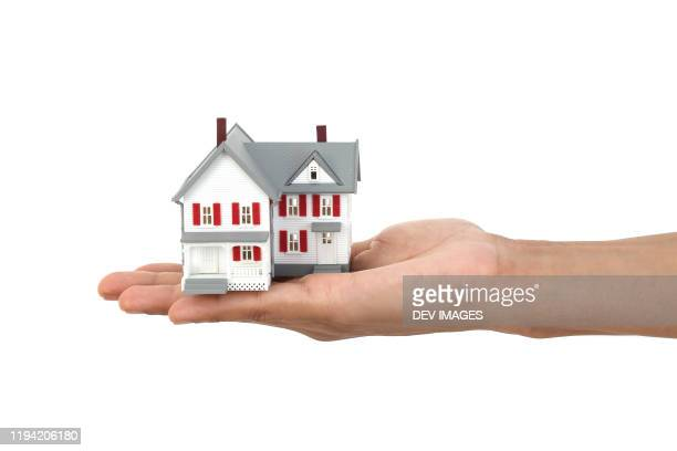 holding model house against white background - housing development stock pictures, royalty-free photos & images