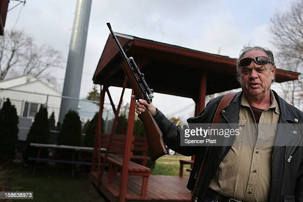 Holding one of three rifles he's turning in Bob Coyle stands outside of a gun buyback event at the Bridgeport Police Department's Community Services...