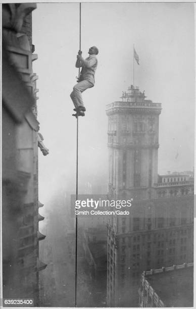 Holding onto a thin rope running downward from the top of a building in Times Square the Human Squirrel performs one of his many outrageous stunts to...