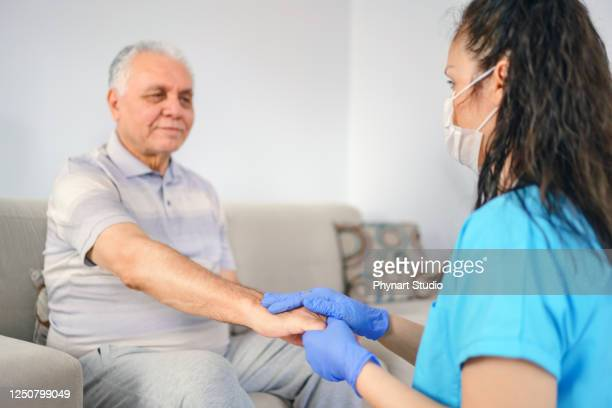 holding patient's hand for health care trust and support - glove stock pictures, royalty-free photos & images