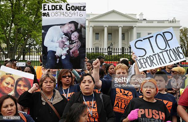 Holding photographs of people who have been arrested for immigration violations people rally in front of the White House to demonstrate against...
