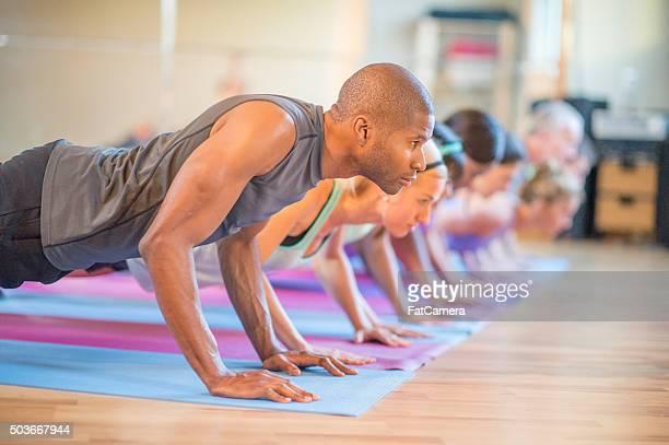 Tenant la position de planche, en cours de Yoga