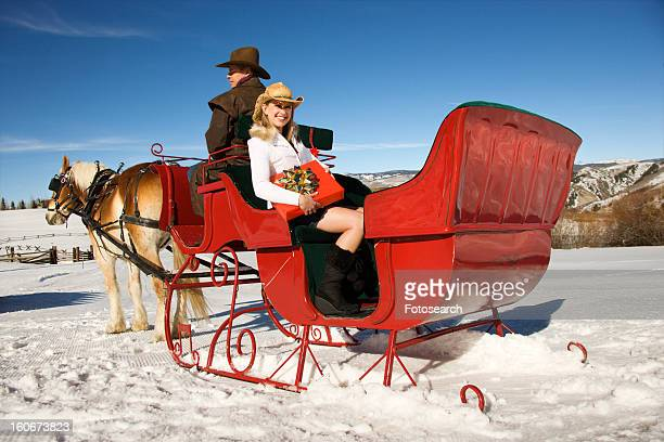holding present in horse-drawn sleigh - cowboy christmas stock pictures, royalty-free photos & images