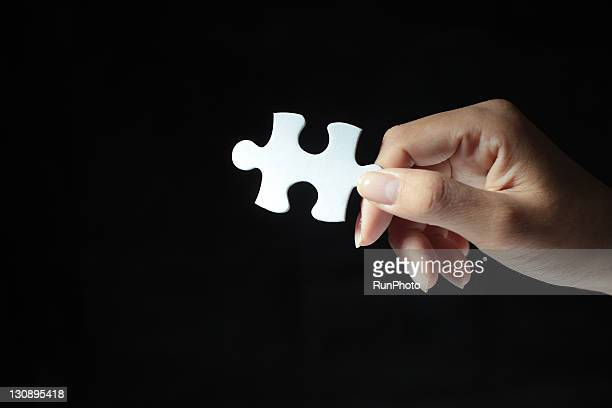 holding puzzle piece,hands close-up