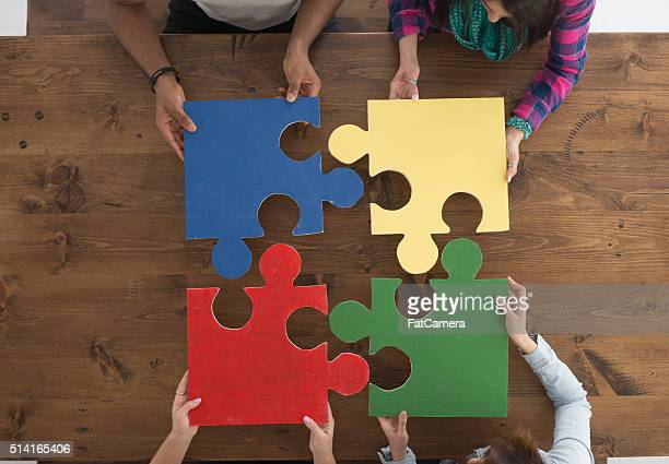 holding puzzle pieces - four people stock pictures, royalty-free photos & images