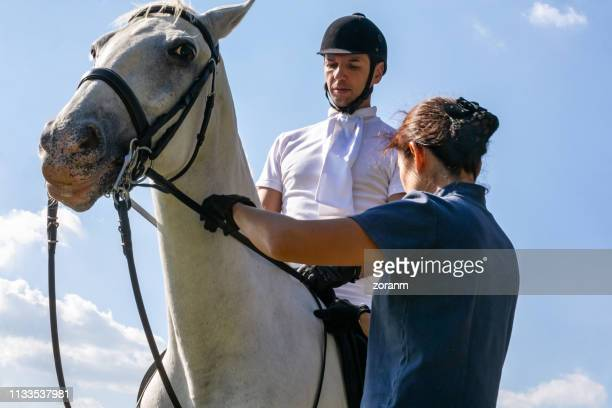 tenant les rênes pour son collègue sur le cheval blanc - cheval blanc photos et images de collection