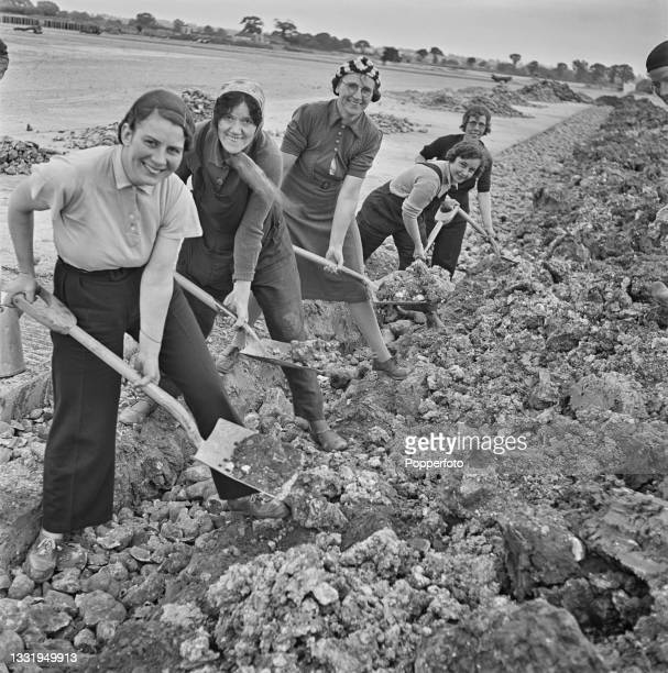 Holding shovels, a group of female construction workers fill in drainage trenches as they carry out rough navvying work on the site of a new...