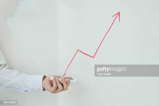 holding smartphone in front of white board