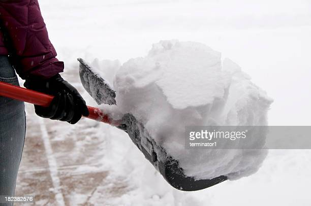 holding snow shovel - snow shovel stock photos and pictures
