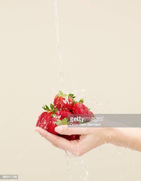 holding strawberries with water splashing on - health2010 ストックフォトと画像