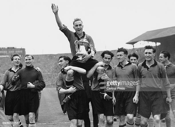 Holding the cup and saluting the crowd Wolverhampton Wanderers captain Billy Wright is held aloft and chaired by Bill Shorthouse and Jesse Pye as...
