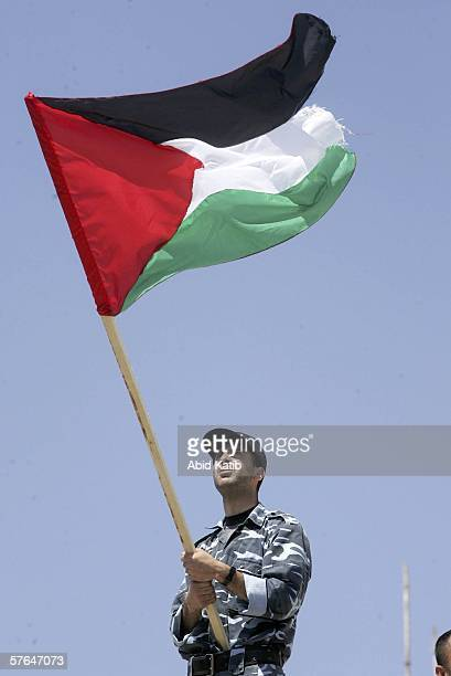 Holding the national flag a Palestinian member of the security forces rallys in support of the Hamasled government May 18 2006 in Gaza City Gaza...