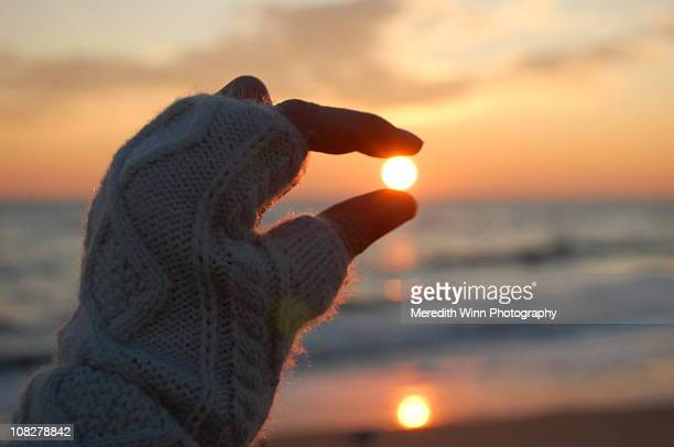 Holding the rising sun between two fingers