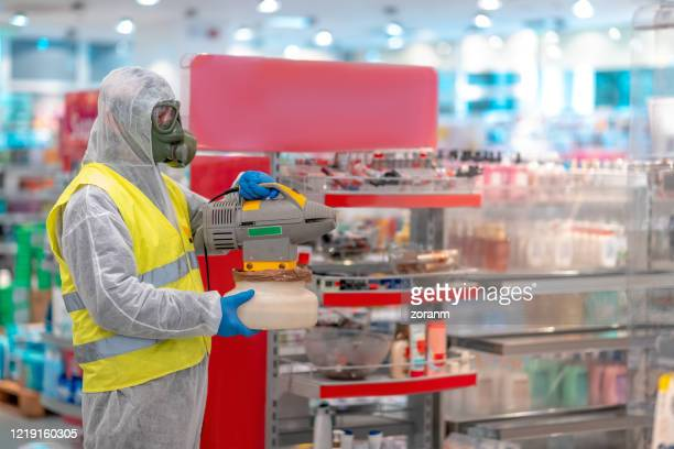 holding up electrostatic sprayer to disinfect supermarket - spraying stock pictures, royalty-free photos & images