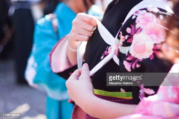 holding up kimono sleeves with tasuki - サッシュ ストックフォトと画像