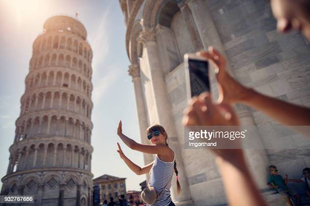 holding up photos of the Leaning Tower of Pisa