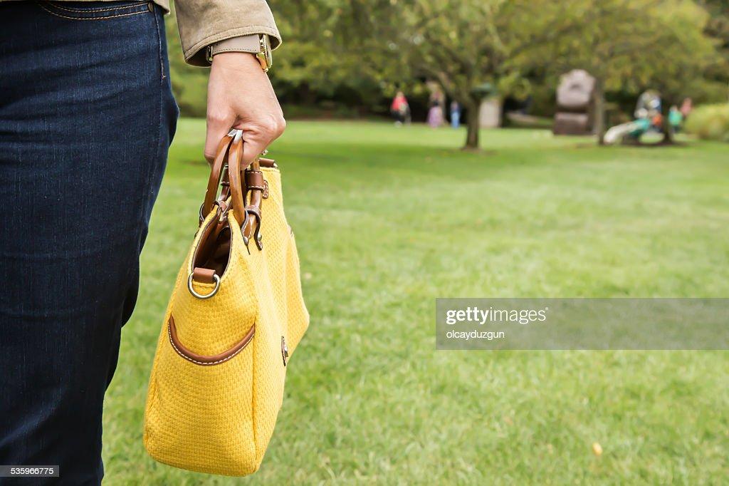 Holding yellow purse : Stock Photo