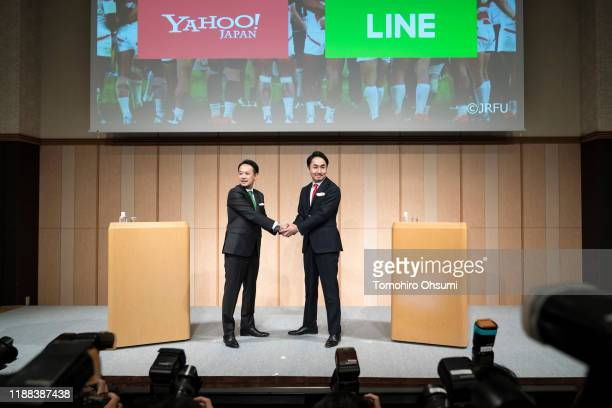 Holdings Corp CEO Kentaro Kawabe and Line Corp CEO Takeshi Idezawa shake hands during a joint press conference on November 18 2019 in Tokyo Japan Z...