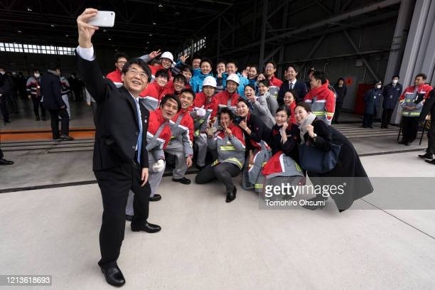 Holdings Inc CEO Shinya Katanozaka takes a photograph with ground staff members during the Tokyo 2020 Olympic Games Flame Arrival Ceremony at the...