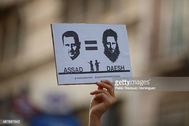 A holds a placard reading 'Assad equal to DAESH' during a demonstration to show solidarity and support for refugees on September 12 2015 in Madrid...