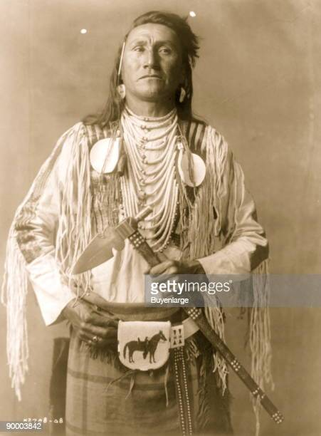Holds The Enemy an Apsaroke man halflength portrait standing facing front wearing several shell necklaces a beaded pouch about his waist and holding...