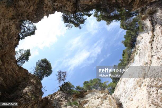 hole in a grotto at rocky coast - grotto stock pictures, royalty-free photos & images