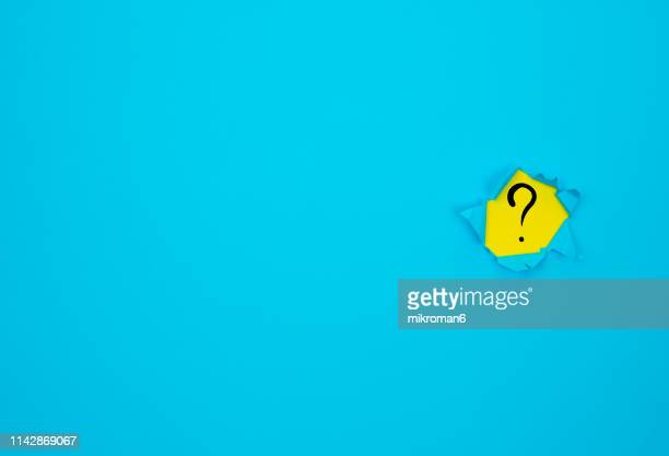 hole in blue page - q&a stock pictures, royalty-free photos & images