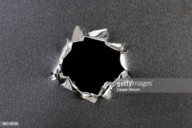 a hole in metal - hole stock pictures, royalty-free photos & images