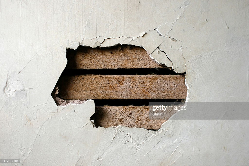 Hole in Plaster Wall - Exposed Wood Paneling : Stock Photo