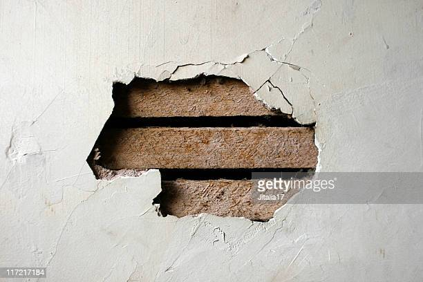hole in plaster wall - exposed wood paneling - demolishing stock pictures, royalty-free photos & images