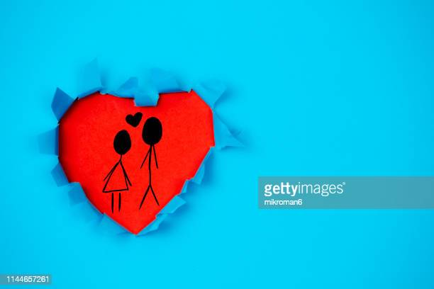 a hole in shape of a heart with family drawing in it - love stock pictures, royalty-free photos & images