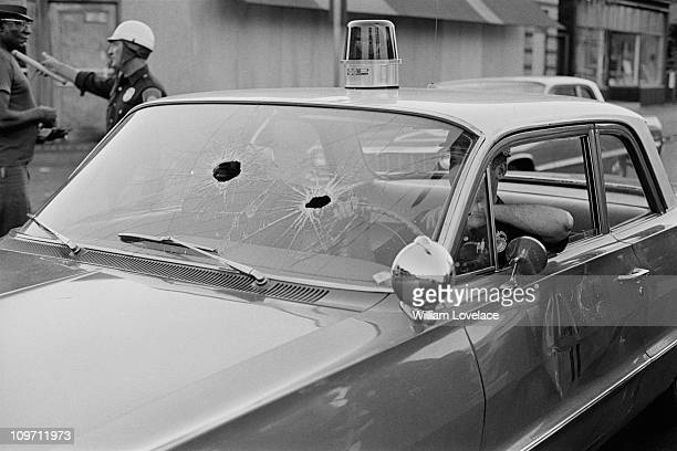 Holes through the windscreen of a police car during the race riot in Rochester New York State late July 1964